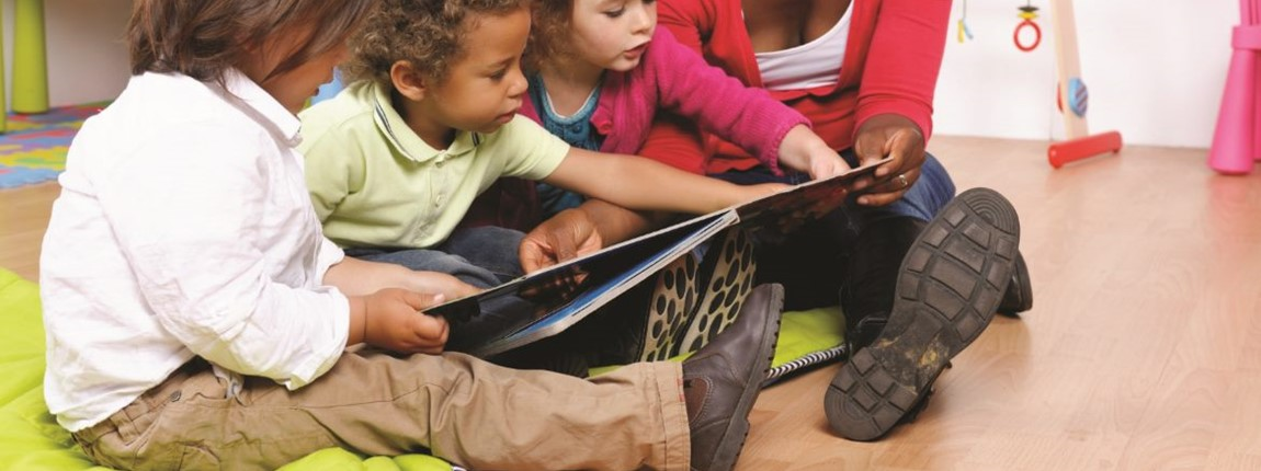 smart-beginnings-three-small-children-on-floormats-reading-together-with-their-teacher